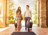 Mladý pár v hotelové chodby po příjezdu, hledají pokoj, drží kufry
