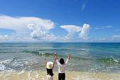 Mladý muž a žena na pláži užívat slunečního záření
