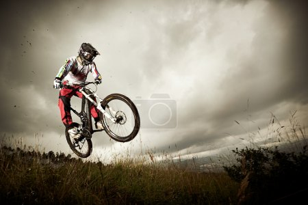 Young man riding a mountain bike downhill style