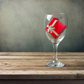 Wine glass with red gift box on wooden table
