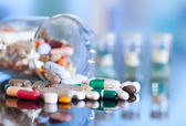 Barevné tablety, kapsle a pilulky na modrém pozadí