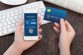 ženské ruce držící kreditní kartu a telefon v kanceláři a mak