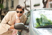 Close up view of an attractive businessman grooming himself using a car mirror outdoors