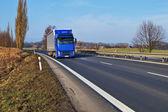 Venkovské krajiny s asfaltovou silnici a modré truck