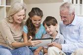 Seniors & Children Grandparents & Grandchildren Using Tablet Com