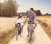 Happy couple cycling outdoors in summer