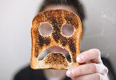 Uomo che sorregge una bruciato fetta di pane tostato con un infelice smiley conept per iniziare male la giornata