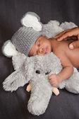 Tredici giorni di età ragazzo neonato in un cappello grigio elefante alluncinetto, dormendo su un elefante di peluche. suo padre è toccare la schiena e il bambino ha uno sguardo dolce di contentezza