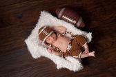 Un ragazzo neonato 12 giorni di età, dormendo in una pelliccia foderato crate e indossando un costume a maglia football americano