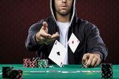 Giocatore di poker, su uno sfondo rosso, gettando due carte asso