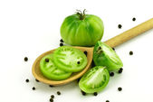 Green tomatoes with wooden spoon