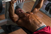 Shirtless body builder doing bench press for chest