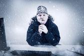 Uomo daffari in un ufficio di freddo con neve e ghiaccio