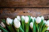 Bílé tulipány na rustikální dřevěné pozadí