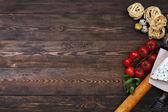 Sfondo di cibo italiano su assi di legno rustici con copyspace, con tagliatelle pasta, pomodori, basilico, formaggio, grossini e condimenti