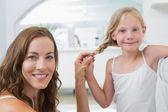 Portrét smějící se ženy pletení vlasy roztomilá holčička