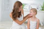 Frau niedliche kleine Mädchen Haare im Bad anpassen