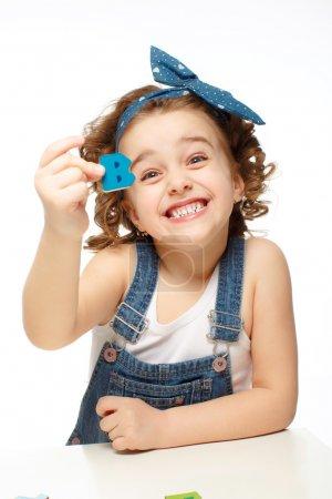 小女孩在玩在字母表中。显示字母 b