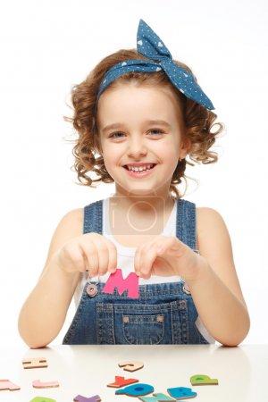 小女孩在玩在字母表中。显示字母 m