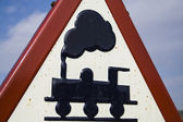 Varovným signálem nosí z úrovňového přejezdu bez bariéry, modrá obloha s mraky