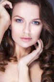 Schöne Brünette Frau mit blauen Augen ohne Make-up, natürliche makellose Haut und Hände in der Nähe von ihr Gesicht
