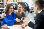 Prodavač auta dát klíč nového vozu mladá atraktivní vlastníkům