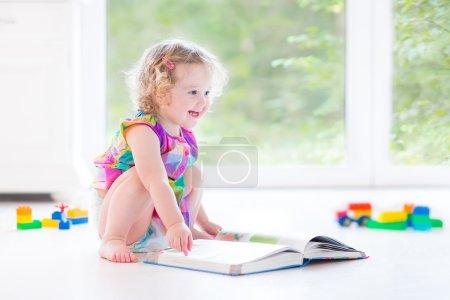 读一本书的金色卷发的女孩
