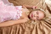 Krásná holčička spí na posteli
