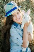 Aranyos tini lány ül előtt szénakazalban fehér nyúl