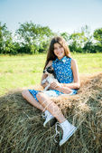 Cute teen girl with puppy sitting on the top of haystack