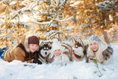 Laughing family and husky dog in winter park