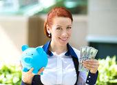 Podnikatelka drží prasátko, dolarové bankovky