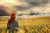 Fashion young red hair woman standing back outdoor on breathtaki