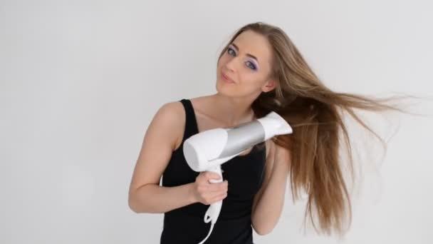 krásná usměvavá dívka sušení rukou vlasy foukat fénem
