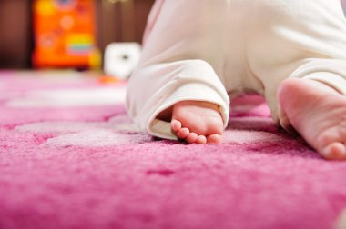 Baby crawling on pink carpet