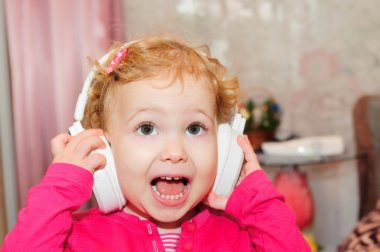 Cute little girl singing in headphones
