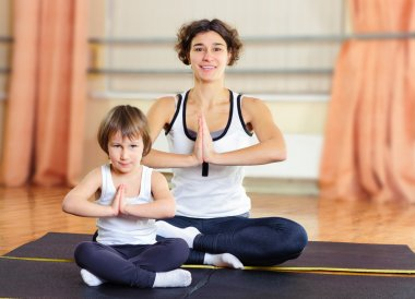 Young mother and little daughter exercising in gym