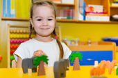 Cute little girl playing in kindergarten