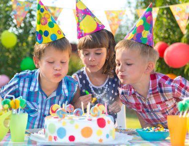 Kids at birthday party blowing candles on cake
