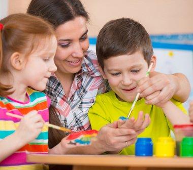 Cute children drawing with teacher at preschool class
