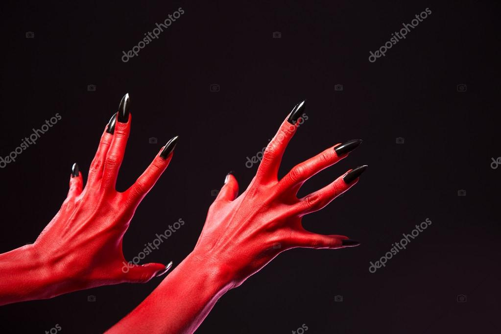 Spooky red devil hands with black nails, real body-art
