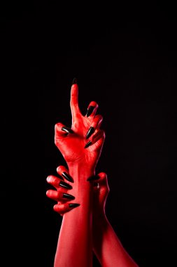 Scary red demonic hands with black nails, real body-art