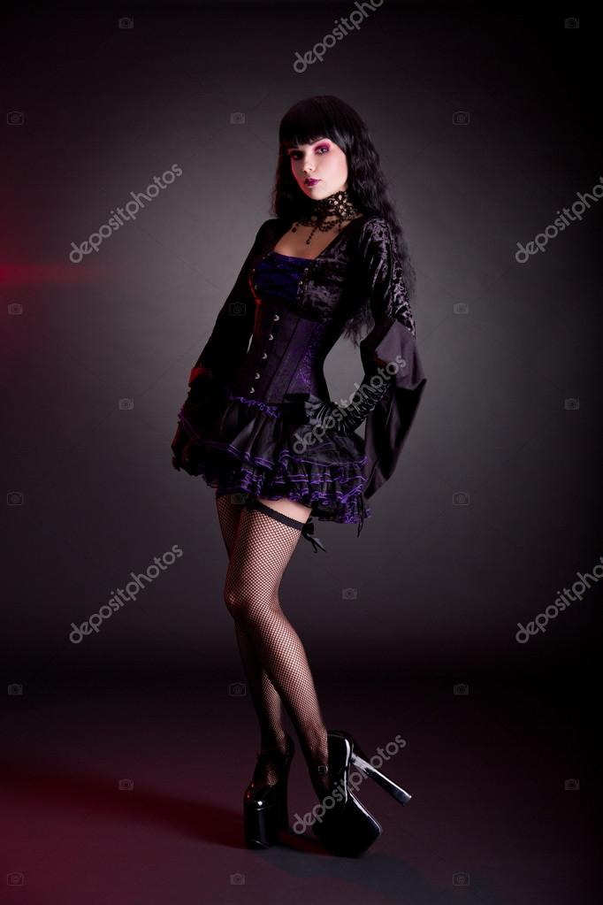 Pretty young woman in Victorian purple and black Halloween outfi