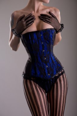 Busty woman wearing black and blue corset