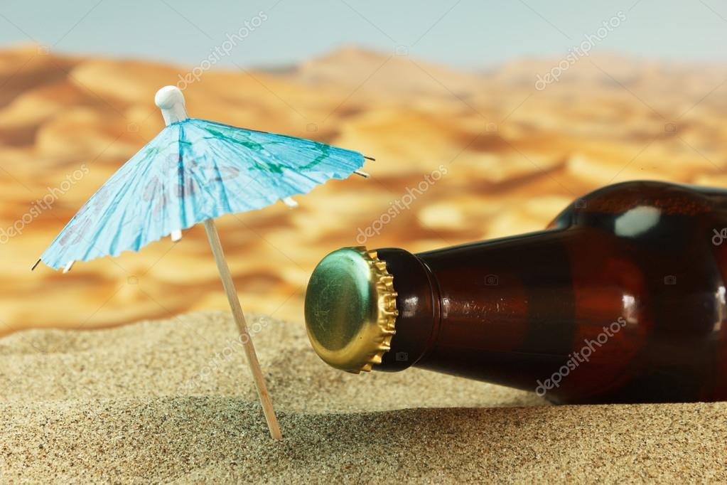 Bottle under an umbrella on the sand