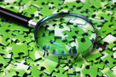 Fotografie magnifying glass on pile of green puzzle