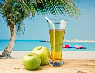 Glass of apple juice on a beach table