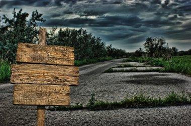 old wooden road sign on a dark deserted road