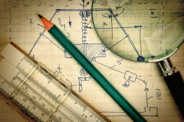 magnifying glass and a slide rule on the old page with the calcu