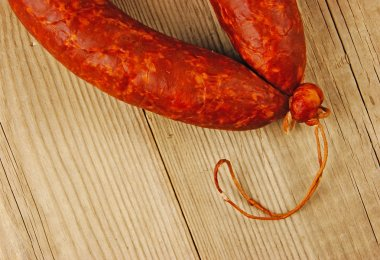 Krakow sausage isolated on the wooden table